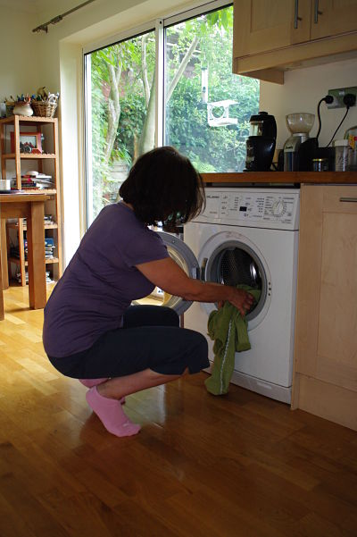 Woman squatting to load washing machine