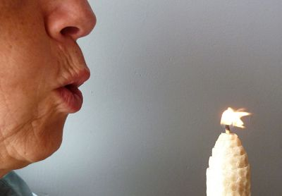 Person blowing out a candle