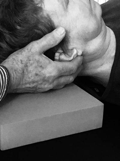 Alexander teacher holding head of client lying on Alexander table